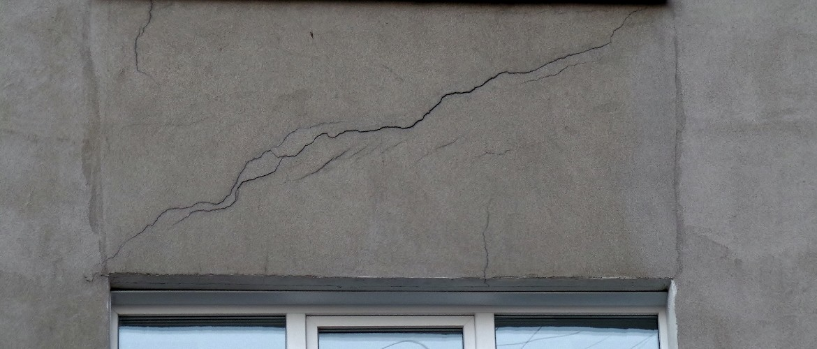 the crack in the wall above the window